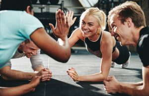 fitness class members hitting high 5